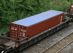 Open top shipping container on train
